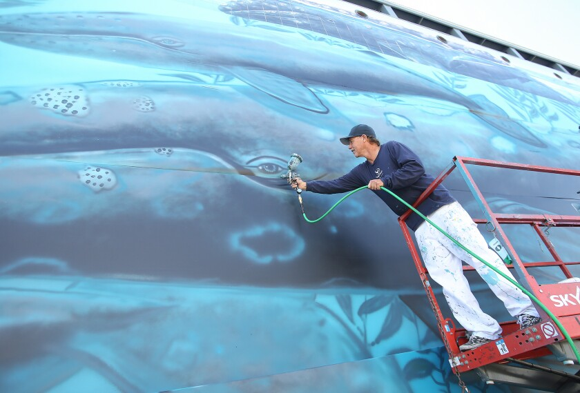"""Artist Wyland adds a touch of airbrush to a whale's eye Friday as he re-creates his original """"whaling wall"""" mural on canvas at the spot of the first one, which he painted in Laguna Beach in 1981."""