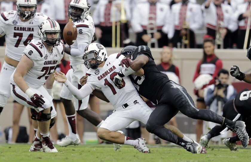 South Carolina quarterback Perry Orth (10) loses the ball as he is hit by Texas A&M defensive lineman Myles Garrett, right, during the second half of an NCAA college football game, Saturday, Oct. 31, 2015, in College Station, Texas. Texas A&M won 35-28. (AP Photo/Eric Gay)
