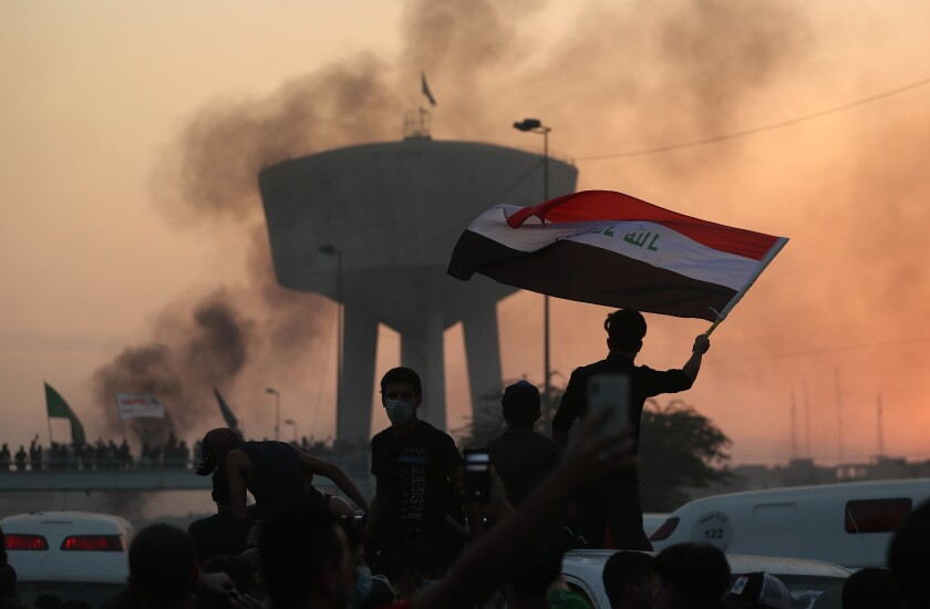 Anti-government protesters wave flags during a demonstration in Baghdad, Iraq, Wednesday, Oct. 2, 2019. Iraqi officials said several protesters have been killed Wednesday and scores injured amid gunfire and clashes in Baghdad. (AP Photo/Hadi Mizban)