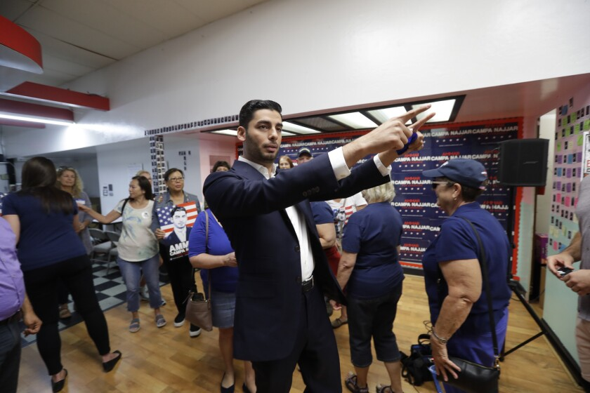 Democratic congressional candidate Ammar Campa-Najjar, center, motions with supporters before canvas
