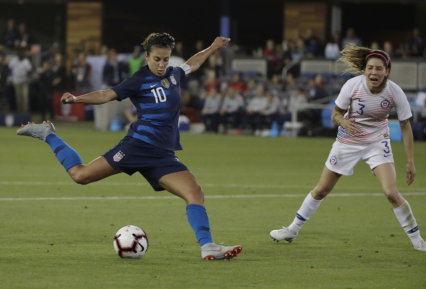 United States' Carli Lloyd (10) kicks the ball past Chile's Carla Guerrero to score a goal during the second half of an international friendly soccer match in San Jose, Calif., Tuesday, Sept. 4, 2018. (AP Photo/Jeff Chiu)