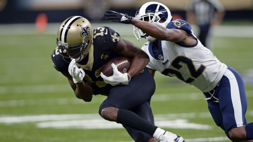 Rams cornerback Marcus Peters (22) tries to tackle New Orleans Saints wide receiver Michael Thomas (13).