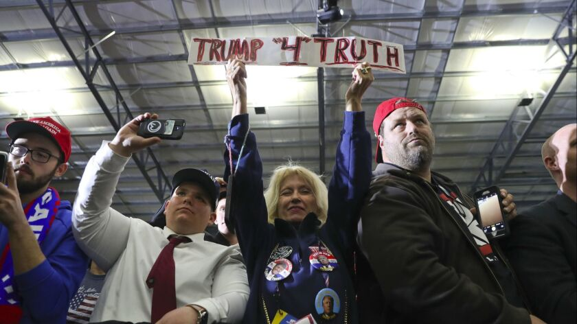 Supporters listen to President Donald Trump speak at a rally on April 28 in Washington, Mich.