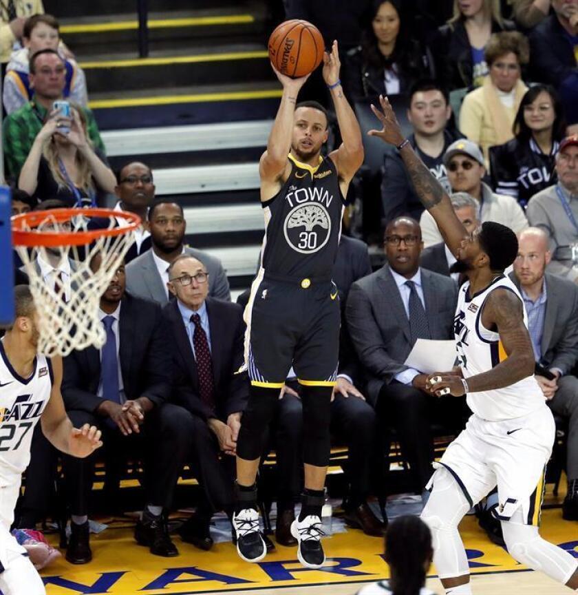 El escolta de los Warriors de Golden Gate Stephen Curry (c) lanza un triple durante el partido de la NBA que enfrentó, este martes 12, a los Jazz de Utah contra los Warriors de Golde State en el Oracle Arena en Oakland, California, Estados Unidos. EFE