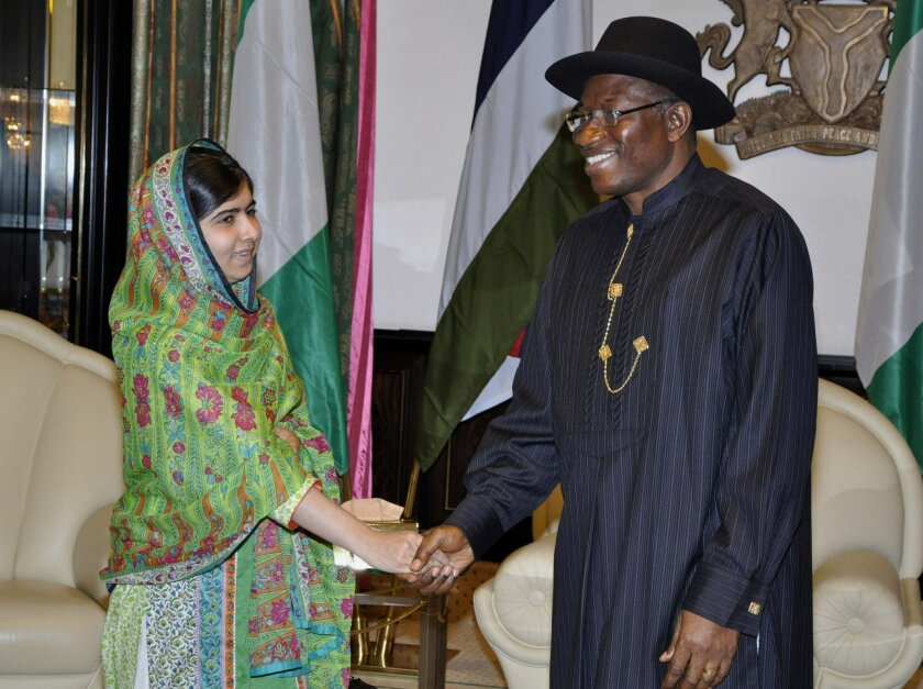 Pakistani activist Malala Yousafzai, left, shakes hands with Nigerian President, Goodluck Jonathan, right, at the Presidential villa, in Abuja, Nigeria, Monday, July 14, 2014. Yousafzai on Monday won a promise from Nigeria's leader to meet with the parents of some of the 219 schoolgirls held by Islamic extremists for three months. Malala celebrated her 17th birthday on Monday in Nigeria with promises to work for the release of the girls from the Boko Haram movement. (AP Photo)