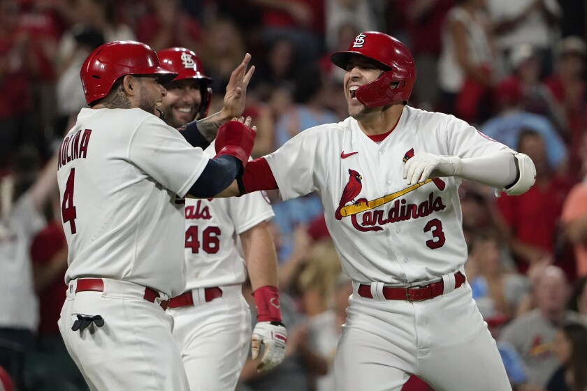 St. Louis Cardinals' Dylan Carlson (3) is congratulated by teammates Yadier Molina (4) and Paul Goldschmidt after hitting a grand slam during the eighth inning of a baseball against the San Diego Padres game Friday, Sept. 17, 2021, in St. Louis. (AP Photo/Jeff Roberson)