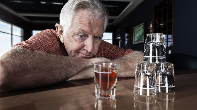 A senior adult man contemplates on taking another drink at a bar