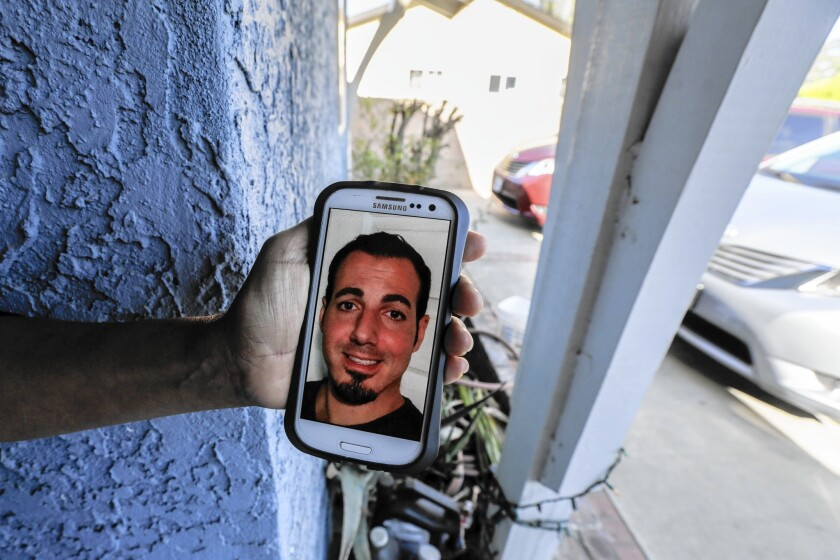 Next-door neighbor Maria Gomez holds her phone displaying a photo of Amier Issa, who was allegedly killed by his father at the family's North Hills home last week.