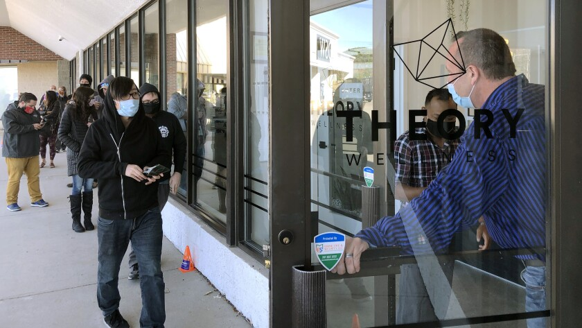 Buyers are let in to purchase cannabis products at Theory Wellness on Friday, Oct. 9, 2020, in South Portland, Maine. Friday is the first day of legal marijuana sales for adult recreational use in the state. (AP Photo/David Sharp)