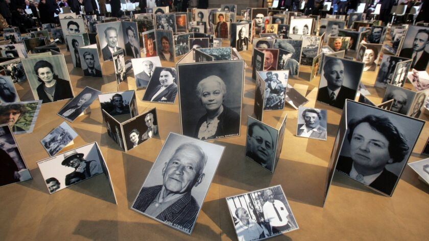Pictures of French people who rescued Jews from the Nazis during WW II are displayed during a cere