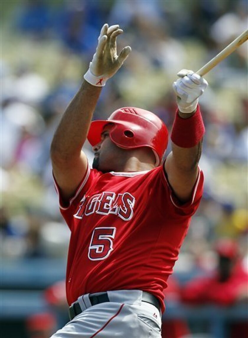 Los Angeles Angels' Albert Pujols hits a solo home run against the Los Angeles Dodgers in the first inning of a Freeway Series exhibition baseball game at Dodger Stadium in Los Angeles, Wednesday, April 4, 2012. (AP Photo/Reed Saxon)