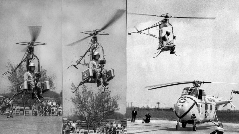 April 15, 1957: The Pinwheel, a rocket-powered, strap-on-the-back helicopter, rises and hovers over a larger craft during its first demonstration.