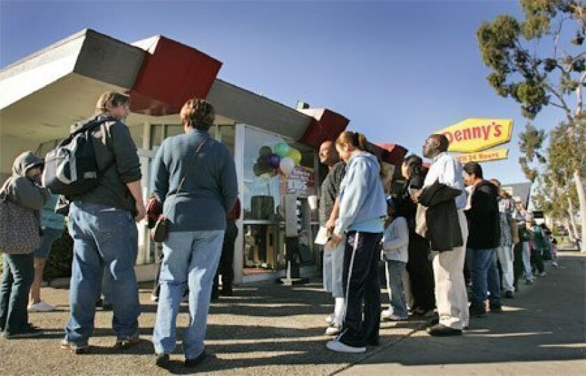 Patrons waited in line outside the Denny's restaurant on El Cajon Boulevard in North Park for a free Grand Slam breakfast. The promotion was aired Sunday during the Super Bowl. (Howard Lipin / Union-Tribune)