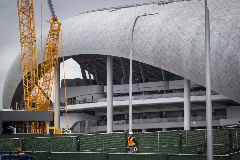 Construction workers work on the SoFi Stadium in Inglewood on March 19.