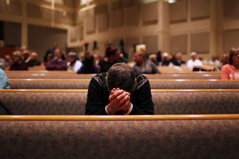 A member of the community prays before the start of the Kalamazoo Community Prayer Service at Centerpoint Church in Kalamazoo, Mich., Sunday, Feb 21, 2016. A gunman who seemed to choose his victims at random opened fire Saturday outside an apartment complex, a car dealership and a restaurant in Michigan, killing six people in a rampage that lasted nearly seven hours, police said. (Andraya Croft/Detroit Free Press via AP)