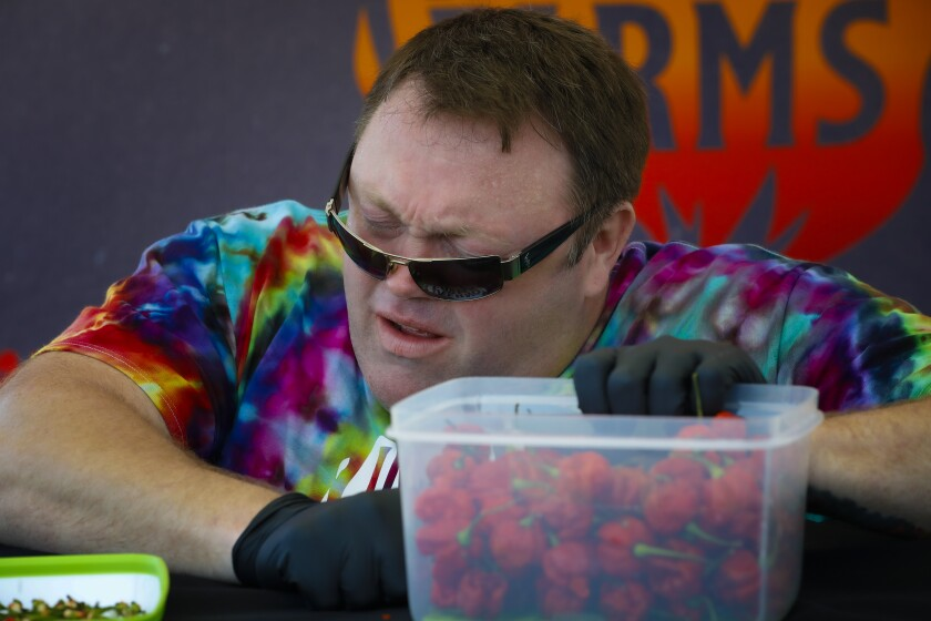 Greg Foster dropped to his knees in his attempt to set a world record of eating 123 Carolina Reaper chilis.