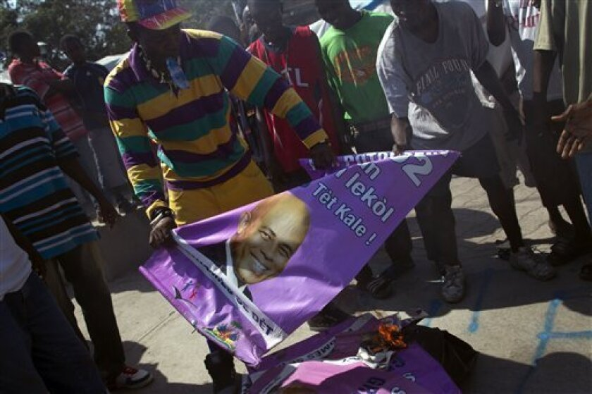 Demonstrators burn signs with images of Haiti's President Michel Martelly during a protest in Port-au-Prince, Haiti, Tuesday, Feb. 7, 2012. (AP Photo/Ramon Espinosa)