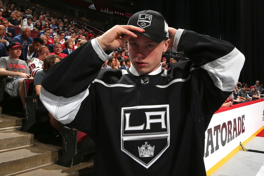 Jaret Anderson-Dolan puts on a Kings hat after being selected 41st overall by the team in the 2017 NFL Draft.