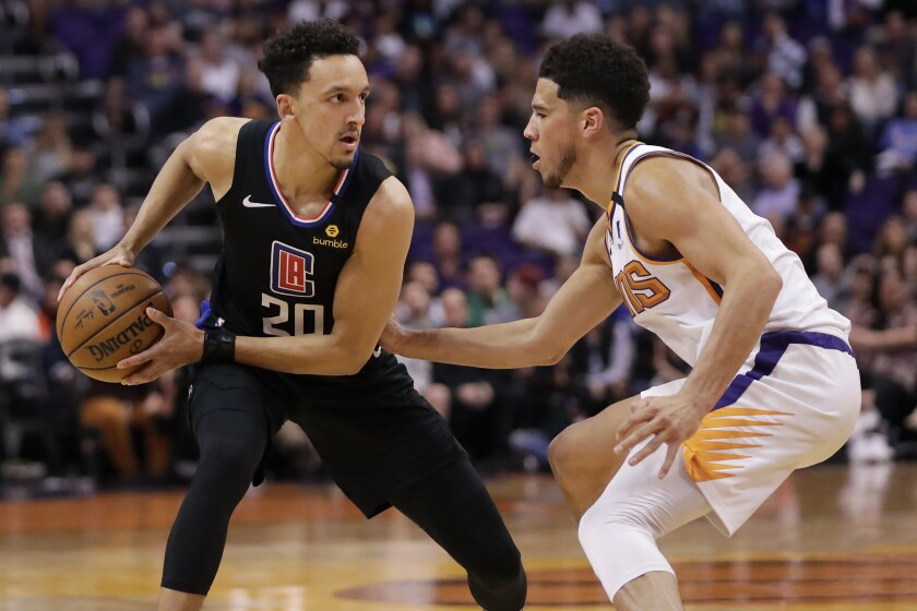 Clippers guard Landry Shamet looks to pass as Phoenix Suns guard Devin Booker defends on Feb. 26 in Phoenix.
