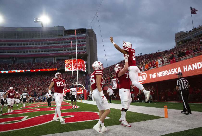 Nebraska's Matt Sichterman (70) lifts quarterback Adrian Martinez (2) in celebration of his touchdown alongside Wyatt Liewer (85) during the first half of an NCAA college football game against Northwestern, Saturday, Oct. 2, 2021, at Memorial Stadium in Lincoln, Neb. (AP Photo/Rebecca S. Gratz)