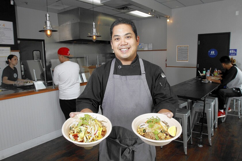 Lawrence Sevilla holds a chicken and rice bowl, left, along with a meatball and noodles bowl, right, at The Asian Project in Burbank, photographed on Thursday, May 22, 2014.