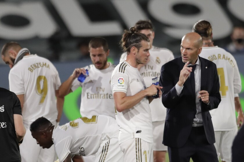 Real Madrid's head coach Zinedine Zidane, right, talks with Real Madrid's Gareth Bale during the Spanish La Liga soccer match between Real Madrid and Mallorca at Alfredo di Stefano stadium in Madrid, Spain, Wednesday, June 24, 2020. (AP Photo/Bernat Armangue)