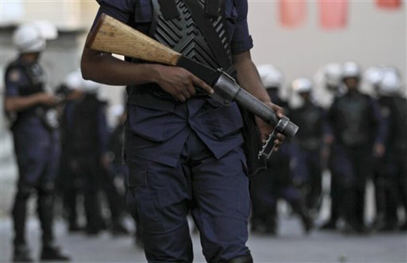 A riot policeman stands guard as others gather behind him during a search of an empty building for Bahraini anti-government protesters Monday, April 9, 2012, in Sanabis, Bahrain, on the edge of the capital of Manama, where demonstrators gathered in support of jailed Bahraini activist Abdulhadi al-Khawaja. U.N. Secretary-General Ban Ki-moon says Bahrain should consider transferring the jailed activist who is on a two-month hunger strike to Denmark for medical treatment on humanitarian grounds. (AP Photo/Hasan Jamali)