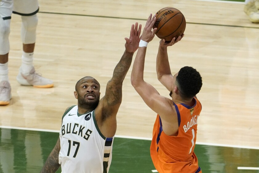FILE - Milwaukee Bucks forward P.J. Tucker (17) tries to block a shot by Phoenix Suns guard Devin Booker (1) during the second half of Game 4 of basketball's NBA Finals in Milwaukee, Wednesday, July 14, 2021. Veteran NBA forward P.J. Tucker signed with Miami this summer, a move that brings his flashy off-court style and his tough on-court ways to the Heat. (AP Photo/Paul Sancya, File)