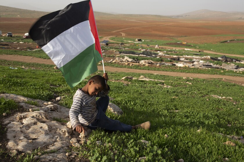 A Palestinian Bedouin boy holds a Palestinian flag after Israeli troops demolished tents and other structures of the Khirbet Humsu hamlet in the Jordan Valley in the West Bank, Wednesday, Feb. 3, 2021. A battle of wills is underway in the occupied West Bank, where Israel has demolished the herding community of Khirbet Humsu three times in as many months, displacing dozens of Palestinians. Each time they have returned and tried to rebuild, saying they have nowhere else to go. (AP Photo/Maya Alleruzzo)