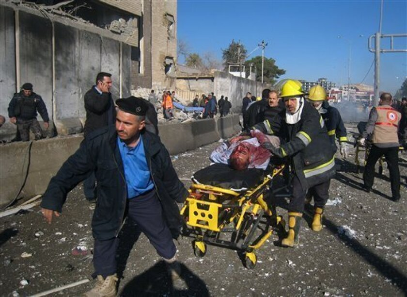 Iraqi firefighters evacuate a victim at the scene of a bomb attack in Kirkuk, 180 miles (290 kilometers) north of Baghdad, Iraq, Sunday, Feb. 3, 2013. A suicide car bomber joined by other suicide attackers on foot assaulted a provincial police headquarters in a disputed northern Iraqi city killing