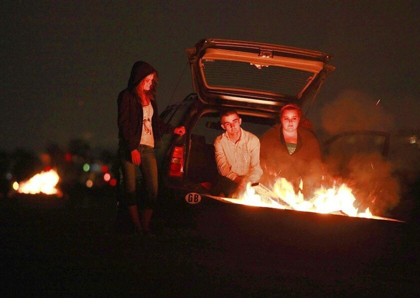 Chiarra Bone, 18, of Clairemont, Dimitri Hazelton, 19, of Serra Mesa and Sharron Fonseca, 19, of San Diego gathered last night near a fire pit on Fiesta Island. The city plans to remove its 186 shoreline fire rings to save maintenance costs, but the state Coastal Commission is requiring a permit first.