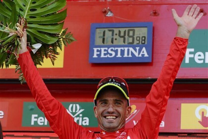 Juan Jose Cobo from Spain, wearing the overall leader's red jersey reacts from the podium after the 20th stage of the Spanish Vuelta cycling race over 185 kilometers (114.7-mile) starting in Bilbao and ending in Vitoria, Spain, Saturday, Sept. 10, 2011. (AP Photo/Juan Manuel Serrano Arce)