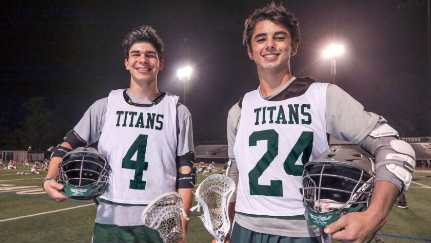 Poway lacrosse players Eli Butler (left) and Marquez White form a dynamic duo for the Titans.