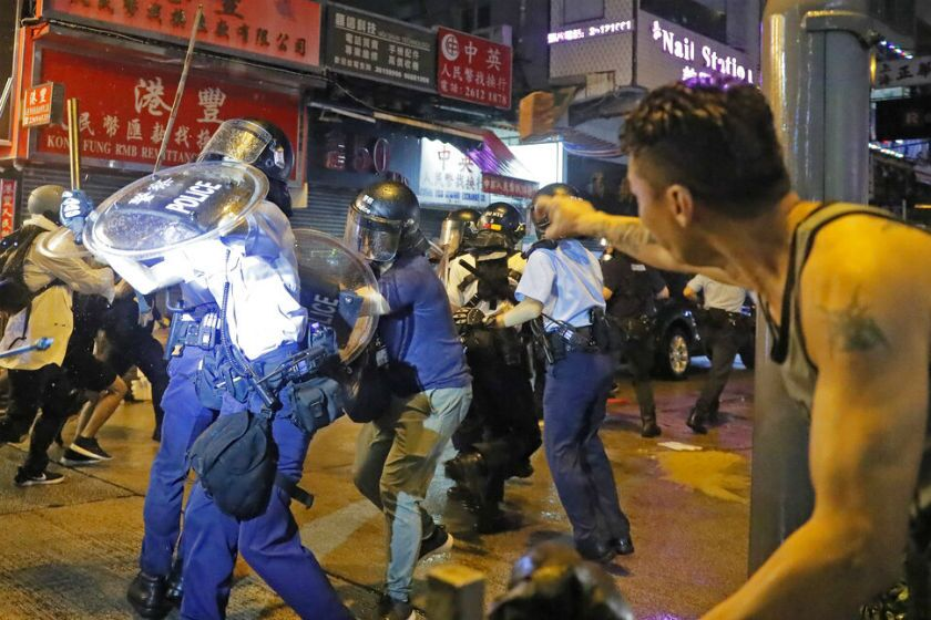 A man tosses a brick at policemen during a protest in Hong Kong on Sunday.