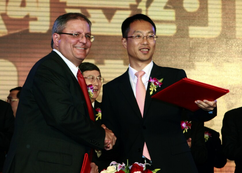 Gerry Lopez, CEO of AMC Entertainment Holdings, left, shakes hands with Zhang Lin, Vice President of Wanda during a signing ceremony for Dalian Wanda Group Co. to acquire AMC Entertainment Holdings.