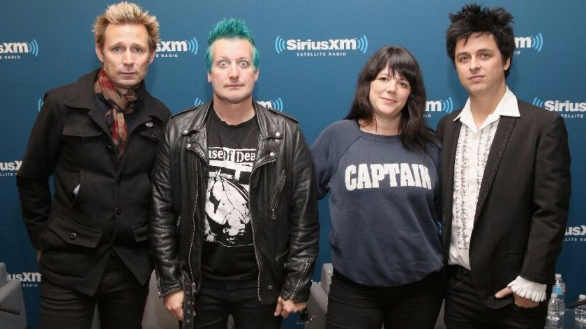 """Mike Dirnt, Tre Cool, and Billie Joe Armstrong of Green Day pose with SiriusXM host Jenny Eliscu during SiriusXM's Oct. 7 """"Town Hall"""" With Green Day."""