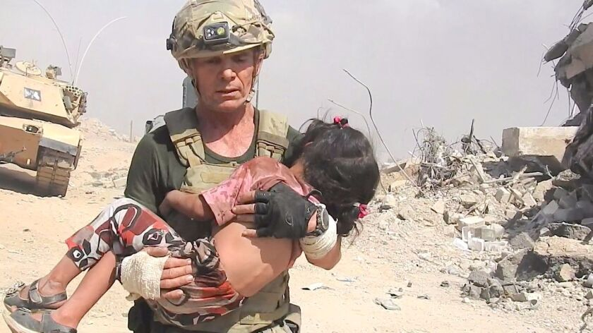 David Eubank carries a child after a dramatic rescue in west Mosul.