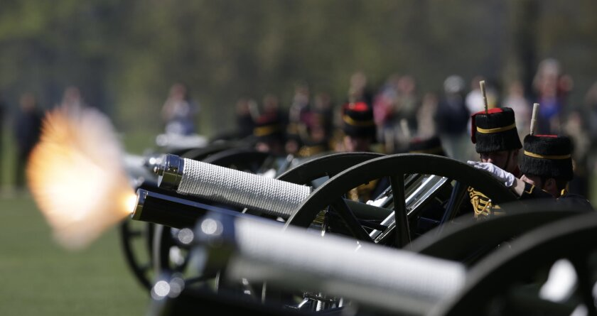 Members of the King's Troop Royal Horse Artillery fire a salvo during a 41 gun Royal Salute to celebrate the birthday of Queen Elizabeth II in Hyde Park in London, Tuesday, April 21, 2015. Some 71 horses pulled six World War I era 13 pounder field guns in the park for the salute. (AP Photo/Alastair Grant)