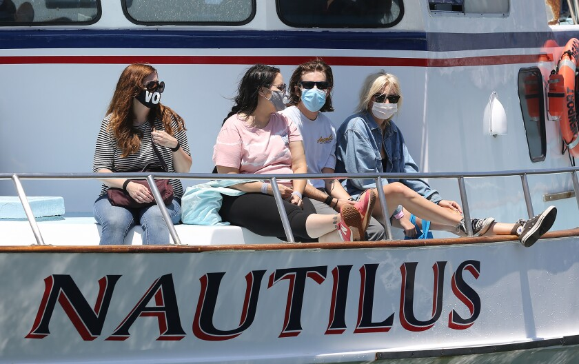 Patrons return from a whale-watching trip aboard the Nautilus while wearing face coverings in Newport Beach on Monday.