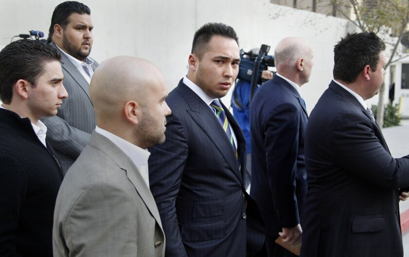 Edward Susumo Azano (middle with blue pin stripe suit and striped blue tie) leaves federal court in San Diego, California, just after his father Jose Susumo Azano was charged with illegally making political donations as a foreign national.