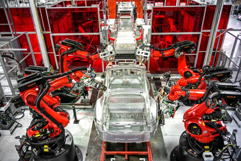 Robots help assemble a car at the Tesla factory in Fremont, Calif.