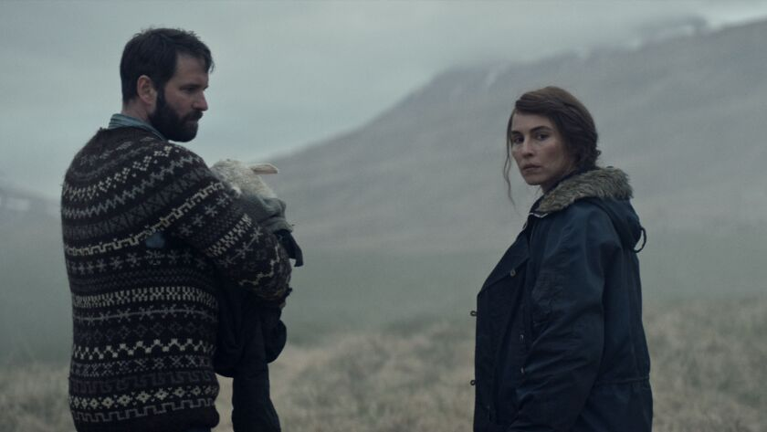 """A man holding an animal stands with a woman in a field in the movie """"Lamb."""""""