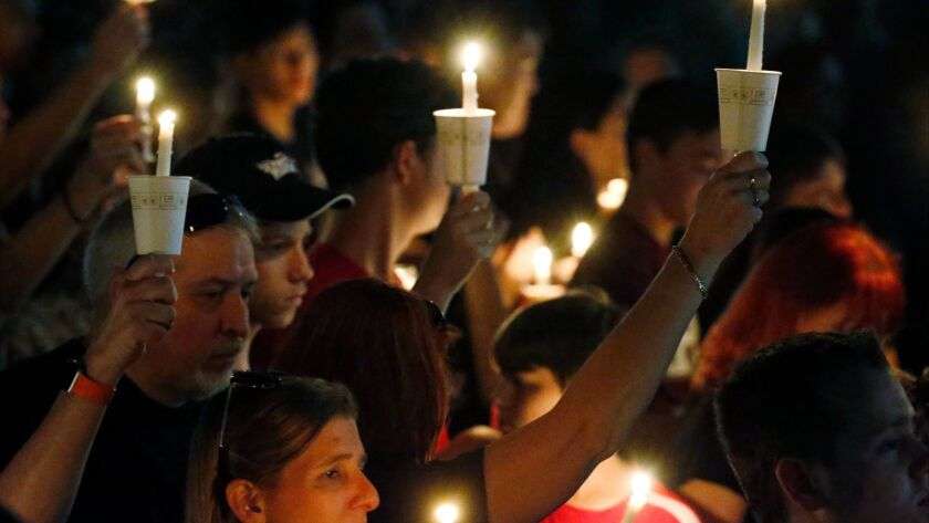 Attendees raise their candles at a vigil for the victims of the shooting at Marjory Stoneman Douglas High School in Parkland, Fla., on Feb. 15, 2018.