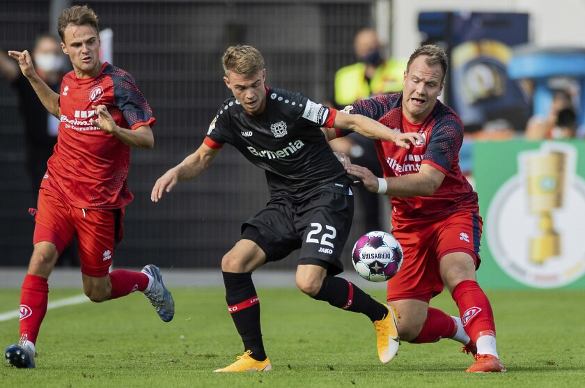 Leverkusen's Daley Sinkgraven, center, and Norderstedt' Jan Lueneburg, right, challenge for the ball during the German Soccer Cup first round match between Bayer 04 Leverkusen and Eintracht Norderstedt in Leverkusen, Germany, Sunday, Sept. 13, 2020. (Rolf Vennenbernd/dpa via AP)