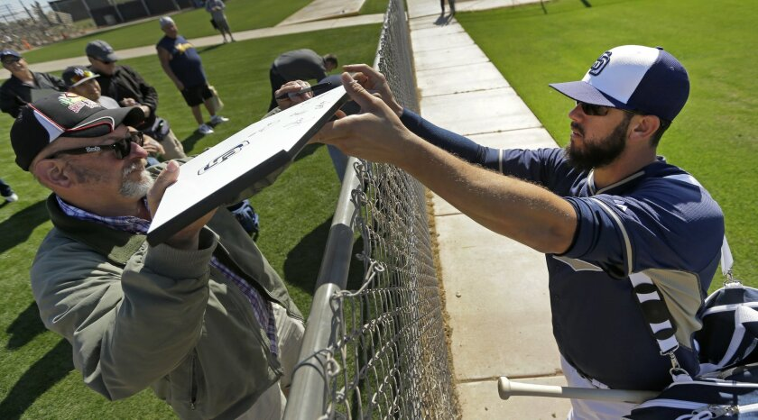 San Diego Padres' James Shields signs autographs during spring training baseball practice Tuesday, Feb. 24, 2015, in Peoria, Ariz. (AP Photo/Charlie Riedel)