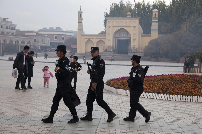 Uighur security personnel patrol near Id Kah Mosque in Kashgar, in the Xinjiang region, in 2017.