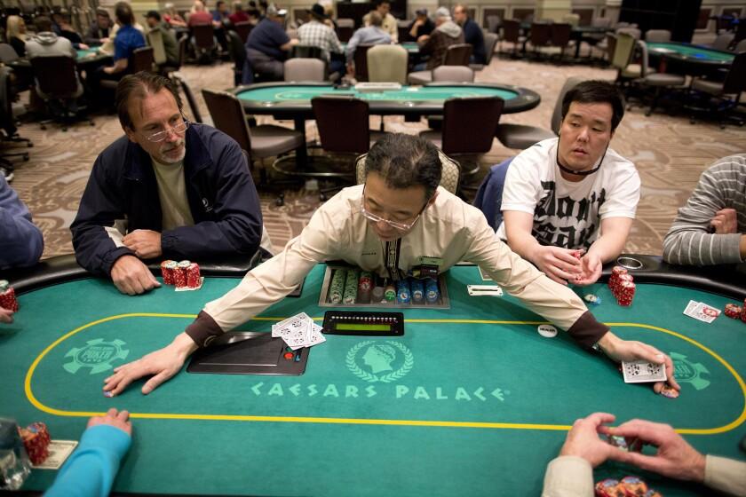 ARCHIVO - En esta fotografía de archivo del 27 de febrero de 2013, el dealer Han Kim, al centro, reúne fichas tras repartir una mano de Texas Hold 'em, una versión de póquer, en el casino Caesar's Palace en Las Vegas. Una caída en el número de personas que juegan bacará y un enero con más eventos hace un año contribuyeron a un descenso de 2,9% en las ganancias de casinos de Nevada el mes pasado, de acuerdo con información de las autoridades divulgada el viernes 26 de febrero de 2016. (Foto AP/Julie Jacobson, archivo)