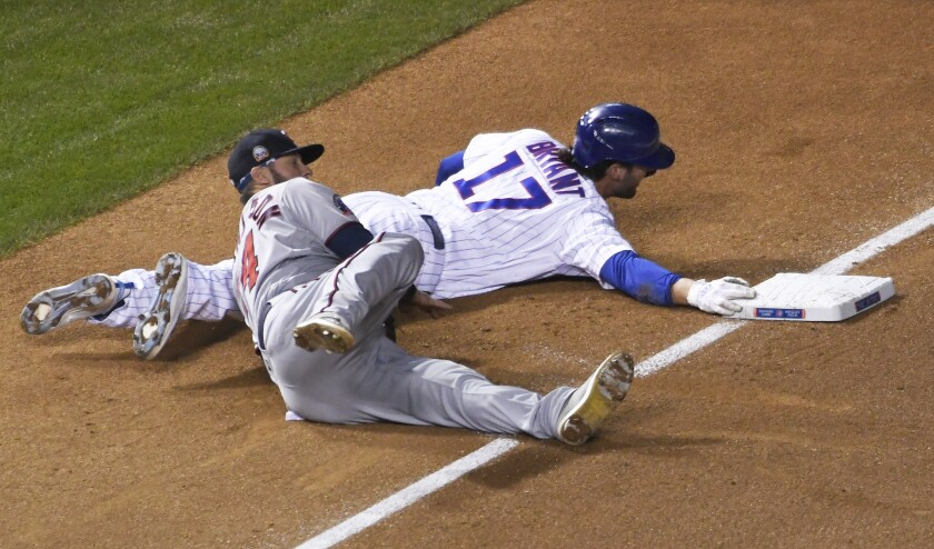 Minnesota Twins third baseman Josh Donaldson (24) tags out Chicago Cubs' Kris Bryant (17) at third base during the first inning of a baseball game, Friday, Sept. 18, 2020, in Chicago. (AP Photo/David Banks)