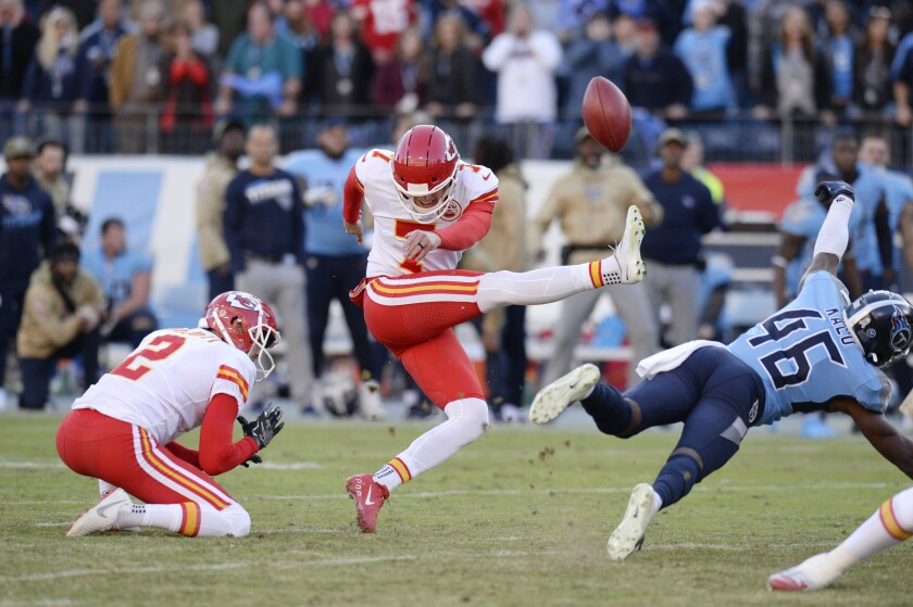 Titans defensive back Joshua Kalu, left, blocks a 52-yard field goal attempt by Chiefs kicker Harrison Butker.