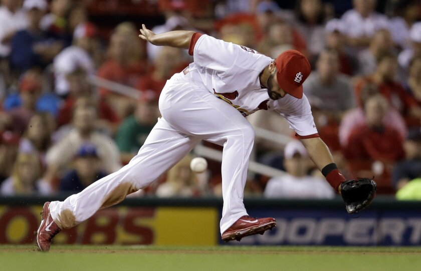 St. Louis Cardinals third baseman Matt Carpenter cannot reach a ball hit for a single by Milwaukee Brewers' Carlos Gomez during the fifth inning of a baseball game Friday, Aug. 1, 2014, in St. Louis. (AP Photo/Jeff Roberson)